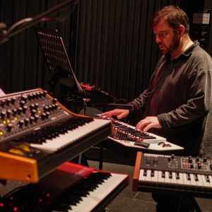 Steven Devine standing, playing, behind bank of synthesizers
